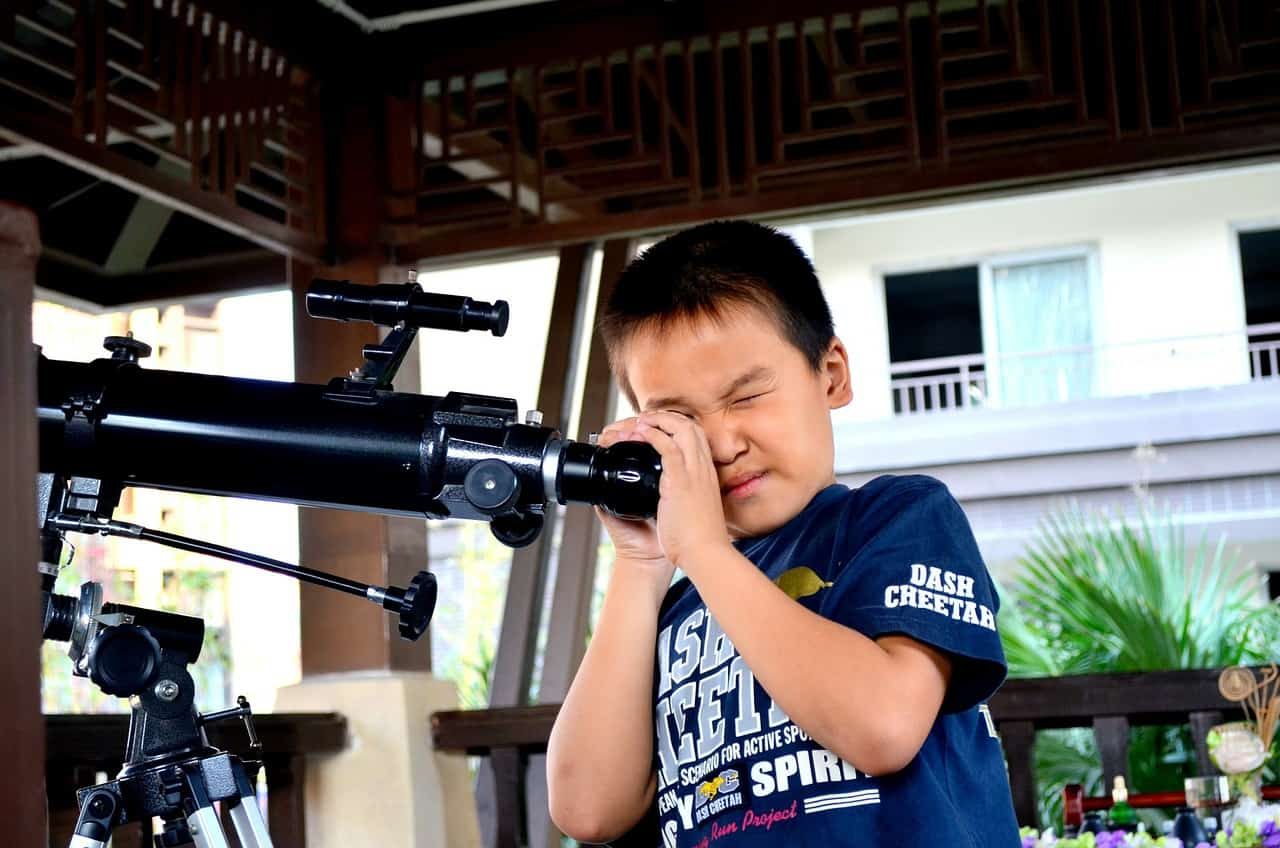 child using a telescope