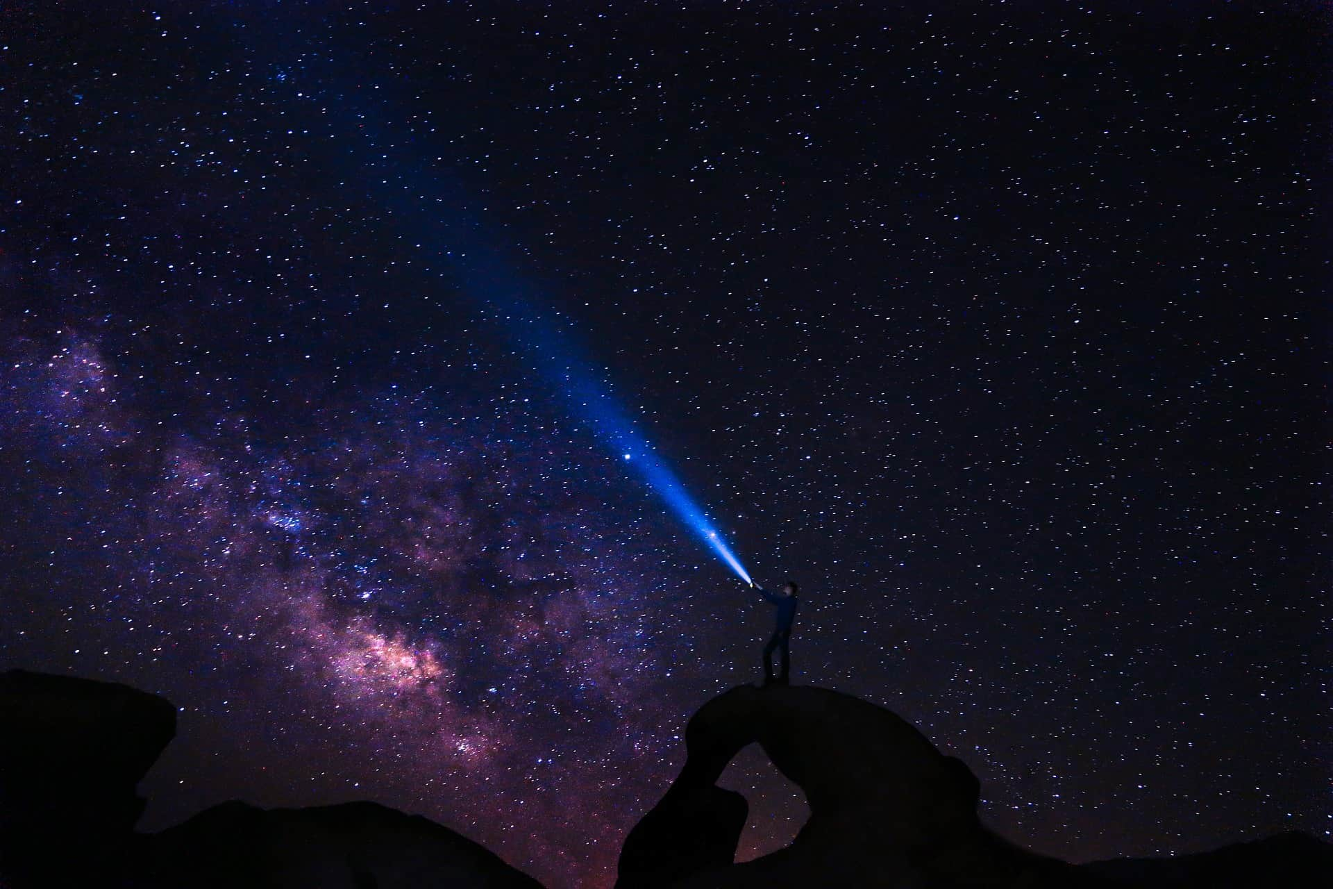 guy standing on a hill trying to see the galaxy
