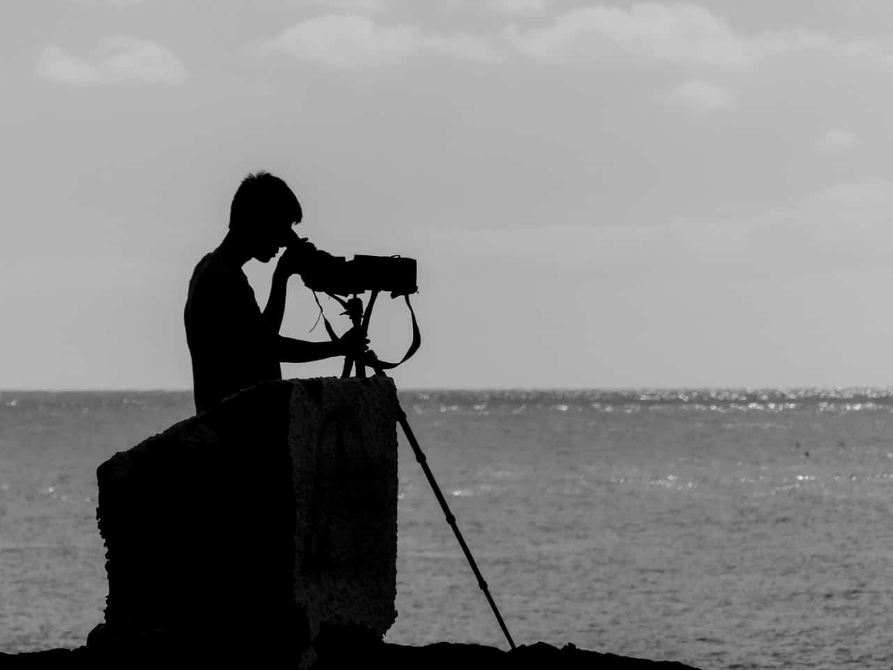 man using a scope to look over the water